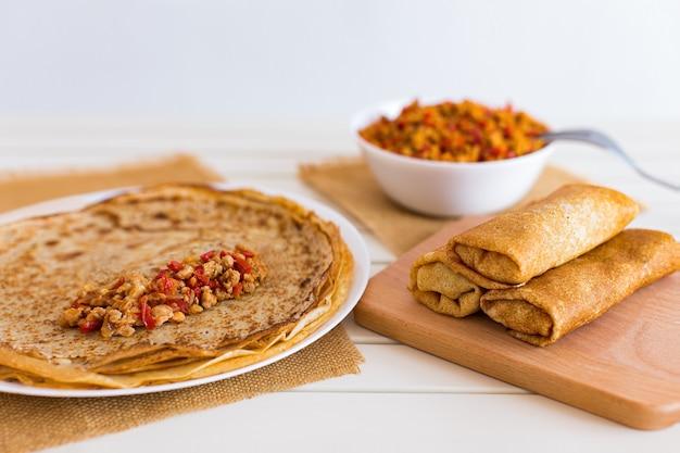 Leckere dünne pfannkuchen mit füllungen. gefüllte crepes mit hackfleisch und paprika. russischer gebratener blini