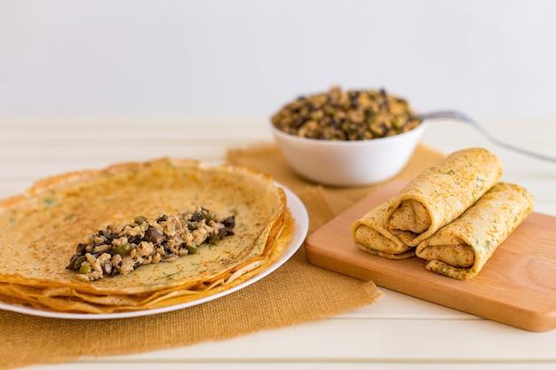 Leckere dünne pfannkuchen mit füllungen. gefüllte crepes mit hackfleischpilzen und marinierter gurke.