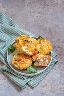 Leckere eimuffins mit süßkartoffel, spinat und zwiebel