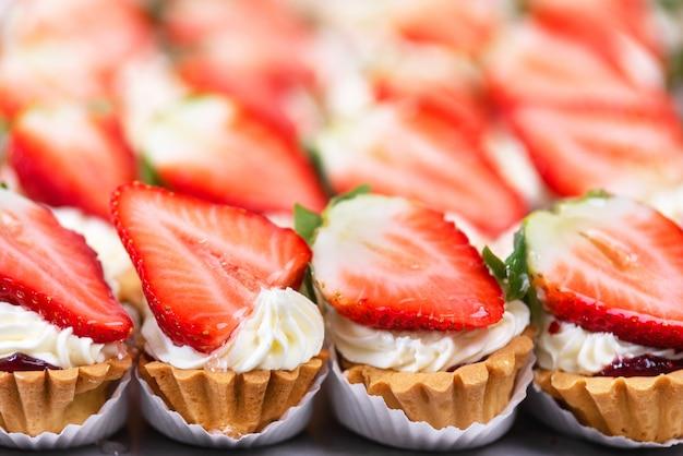 Leckere erdbeer-käsekuchen-törtchen mit frischen erdbeeren.
