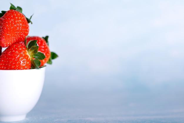 Leckere erdbeeren auf weißem teller vor blauem hintergrund