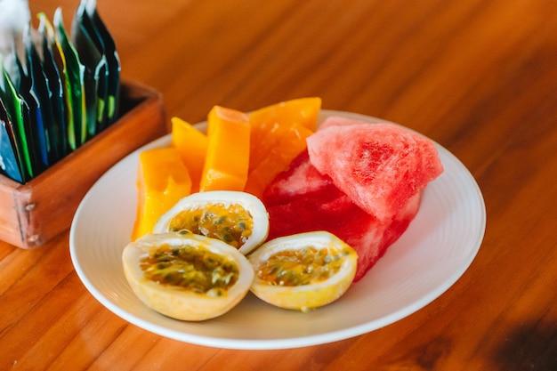 Leckere exotische früchte - reife passionsfrucht, mango zum frühstück im restaurant im freien