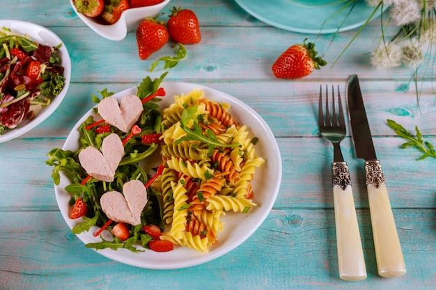 Leckere farbe rotini pasta mit würstchen, frische erdbeere auf einer holzoberfläche
