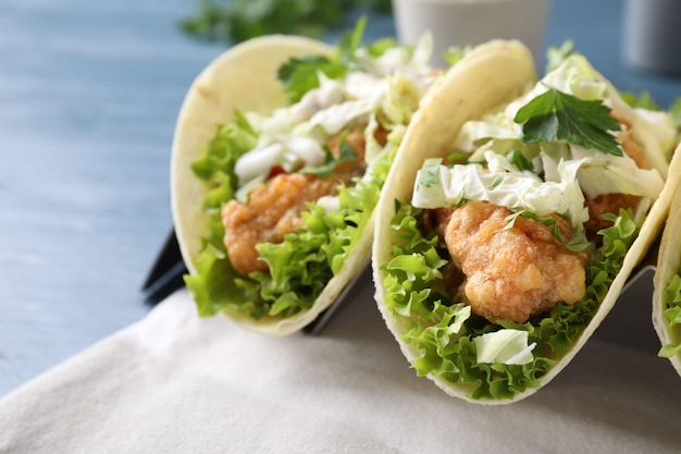 Leckere fisch-tacos im halter auf blauem tisch, nahaufnahme