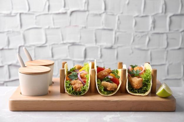 Leckere fisch-tacos mit sauce auf marmortisch