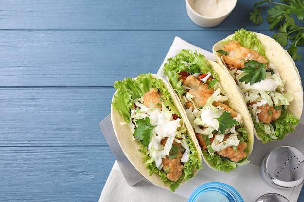 Leckere fisch-tacos serviert auf blauem holztisch, flach. platz für text