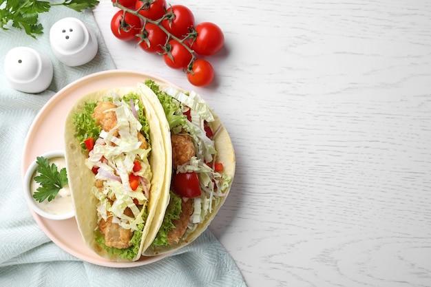 Leckere fisch-tacos serviert auf weißem holztisch, flach. platz für text