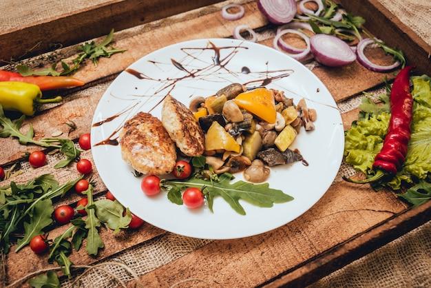 Leckere fleischröllchen mit saurer sahne und salat auf holztisch
