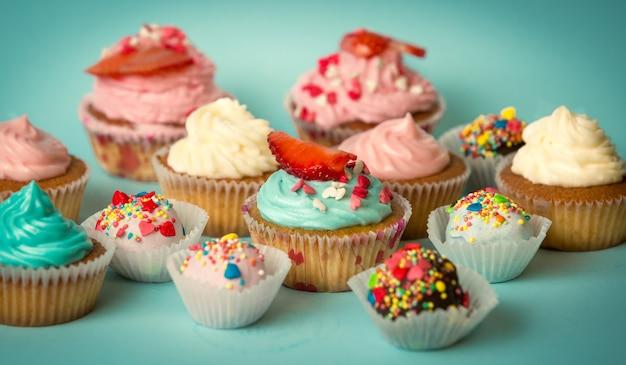 Leckere frisch gebackene cupcakes und bunte bonbons auf türkisfarbenem hintergrund