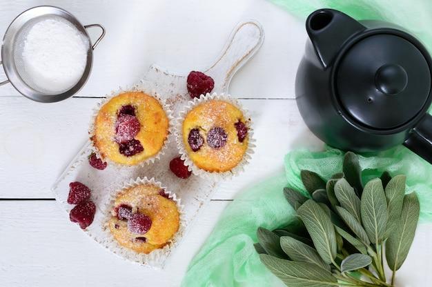 Leckere frisch gebackene muffins mit himbeeren, dekoriert mit puderzucker