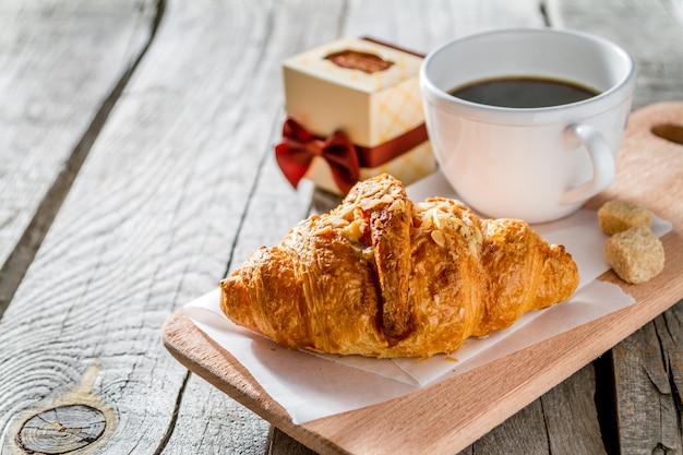 Leckere frische croissants mit kaffee und geschenk