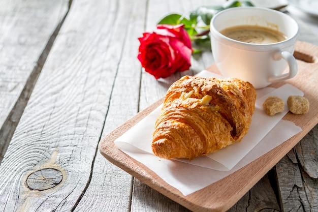 Leckere frische croissants mit kaffee und rose