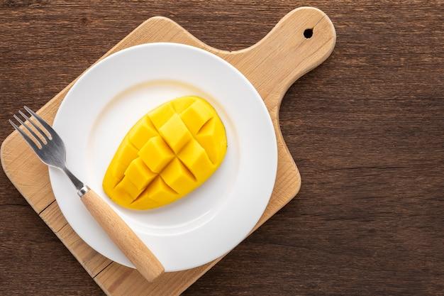 Leckere frische gelbe reife mango mit gabel in einfach weißer keramikplatte auf schneidebrett, draufsicht