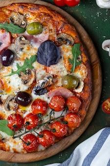 Leckere frische hausgemachte pizza mit schinken, pilzen und tomaten