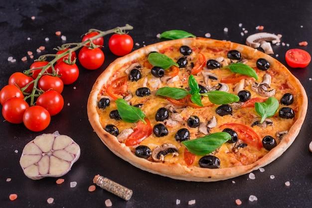 Leckere frische heiße pizza vor einem dunklen hintergrund