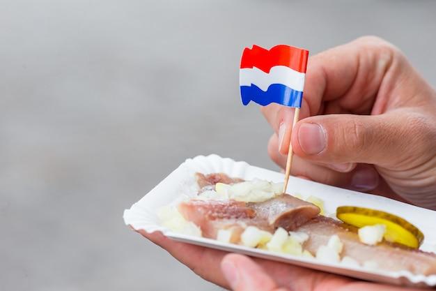 Leckere frische heringe mit zwiebeln und niederlande flagge auf dem wasserkanal in amsterdam. traditionelles holländisches essen