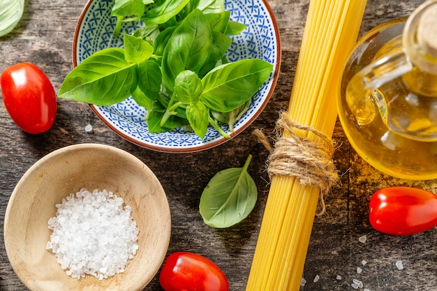 Leckere frische italienische zutaten zum kochen auf altem holzhintergrund. nahansicht. küchen- oder kochhintergrundkonzept