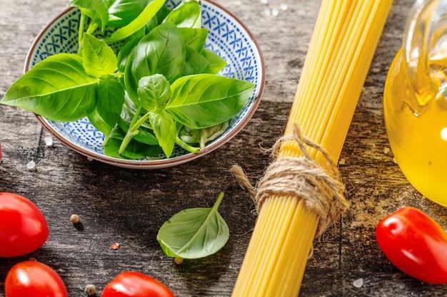 Leckere frische italienische zutaten zum kochen auf altem holzhintergrund. nahaufnahme. küchen- oder kochhintergrundkonzept