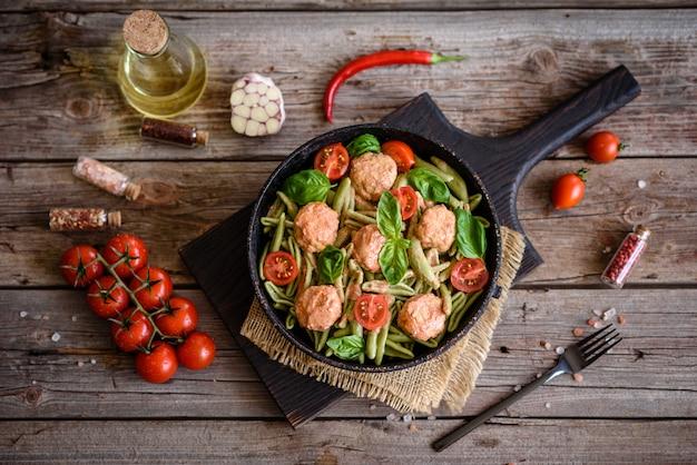 Leckere frische pasta mit fleischbällchen, sauce, kirschtomaten und basilikum