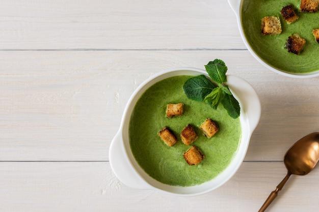 Leckere frische sahnesuppe aus jungen erbsen und minze mit croutons aus weißbrot, gesunde ernährung
