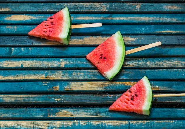 Leckere frische wassermelone. eis mit wassermelone. köstliche wassermelone auf einem blauen hölzernen hintergrund. nahansicht. platz für text.
