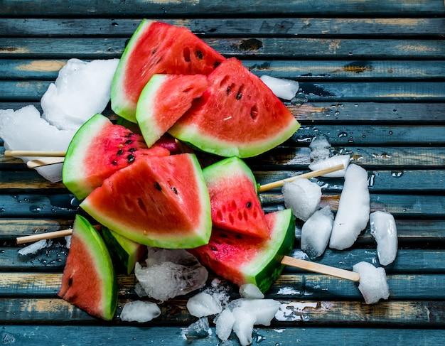Leckere frische wassermelone. eis mit wassermelone. köstliche wassermelone auf einem blauen hölzernen hintergrund. nahansicht.