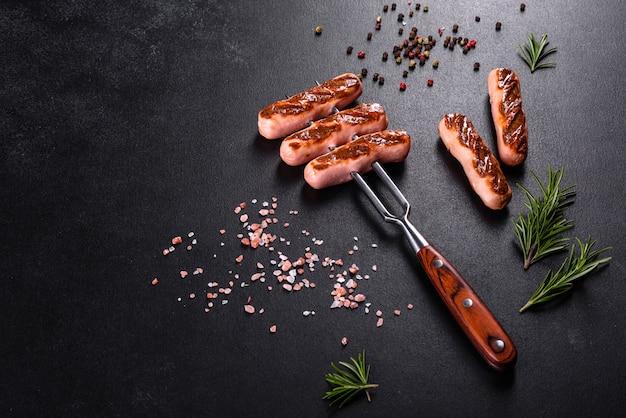 Leckere, frische würste, gegrillt mit gemüsewürzen und kräutern. foto des fertigen gerichts auf einem dunklen betontisch