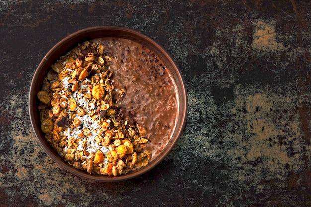 Leckere frühstücksschale mit schokoladenjoghurt und müsli. gesundes frühstück.