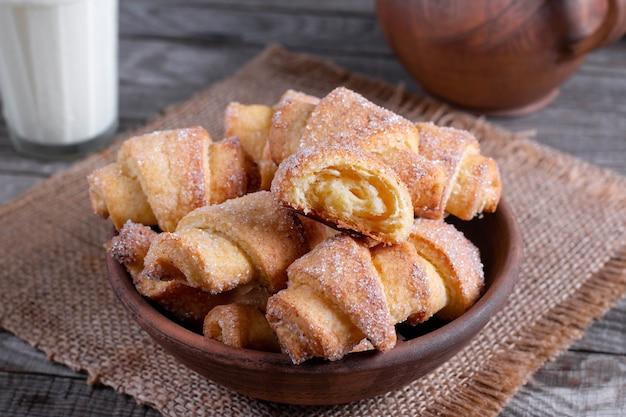 Leckere gebackene gerollte oder bagelplätzchen mit zucker auf rustikalem holztisch