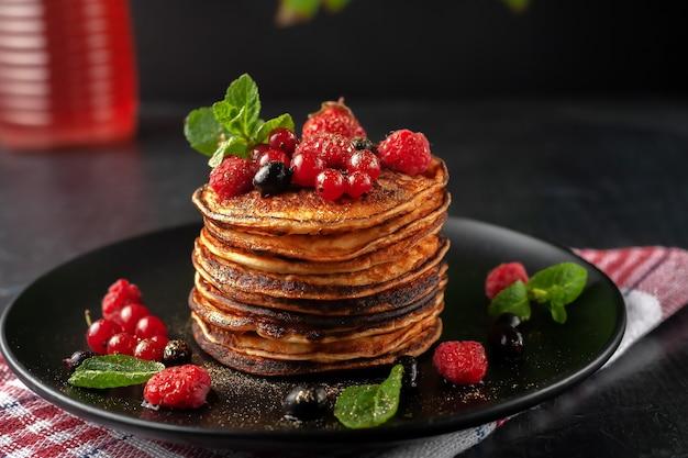 Leckere gebackene pfannkuchen mit frischen früchten von himbeeren, johannisbeeren und erdbeeren auf einem teller