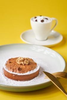 Leckere gebäckkuchen mit nüssen und einer tasse kaffee an einer gelben wand.