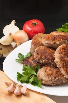 Leckere gebratene fleischkoteletts mit gemüse und kräutern