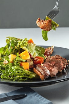 Leckere, gegrillte fleischente mit geröstetem kürbis mit salat auf einer gabel