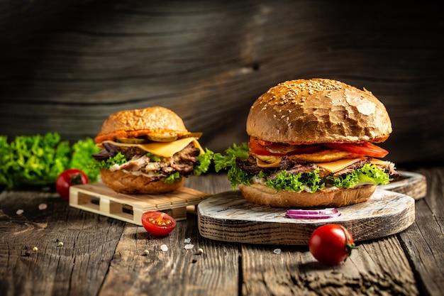 Leckere gegrillte hausgemachte burger mit rindfleisch, tomate, käse, speck und salat auf rustikaler holzoberfläche