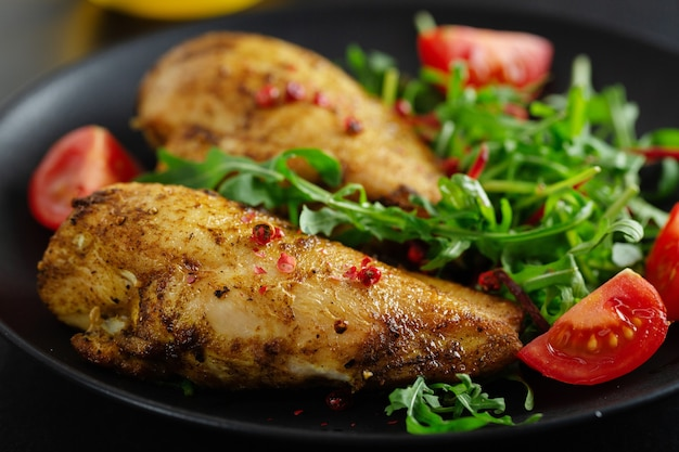 Leckere gegrillte hühnerbrust mit gemüse und salat auf dunklem tisch serviert.