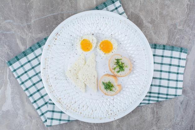 Leckere gekochte eier mit gewürzen und brot auf tischdecke. foto in hoher qualität