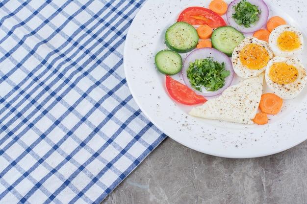 Leckere gekochte eier mit gewürzen und gemüse auf tischdecke. foto in hoher qualität