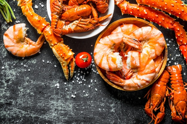 Leckere gekochte garnelen, krabben und krebse. auf dunklem rustikalem tisch