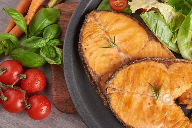 Leckere gekochte lachsfischfilets. gegrilltes lachsfischfilet und frischer grüner salatgemüsetomatensalat. ausgewogenes ernährungskonzept für eine saubere, flexible mediterrane ernährung.