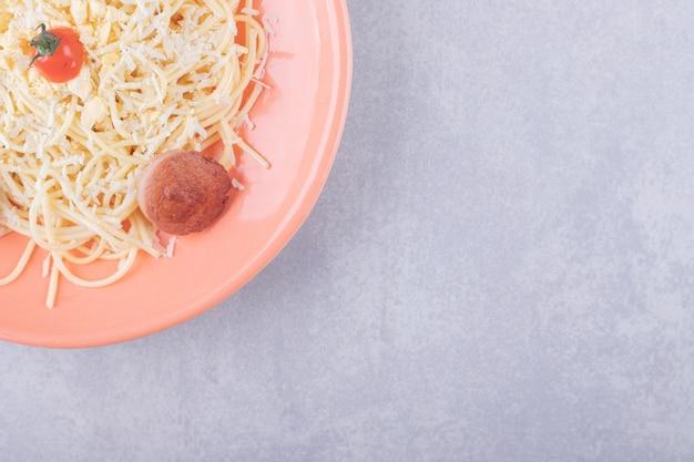Leckere gekochte spaghetti mit würstchen auf orangefarbenem teller.