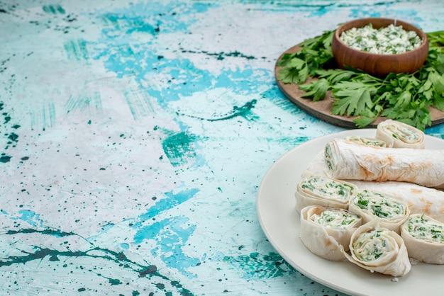 Leckere gemüseröllchen ganz und in scheiben geschnitten mit gemüse und salat auf blauem gemüsesnack