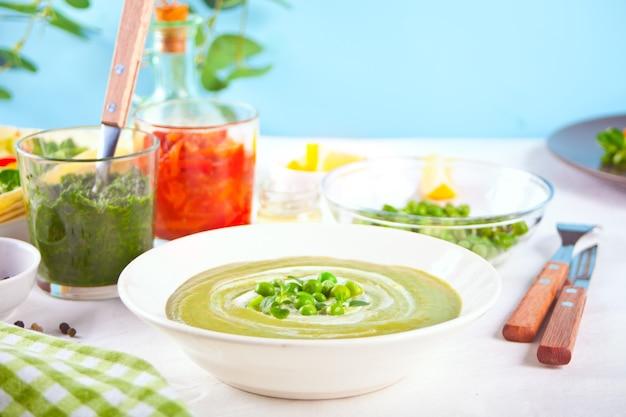 Leckere gemüsesuppe mit kartoffeln, brokkoli, erbsen und spinat auf dem esstisch