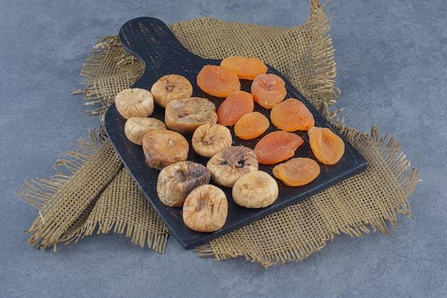Leckere getrocknete früchte auf dem brett, auf dem untersetzer, auf dem marmorhintergrund.