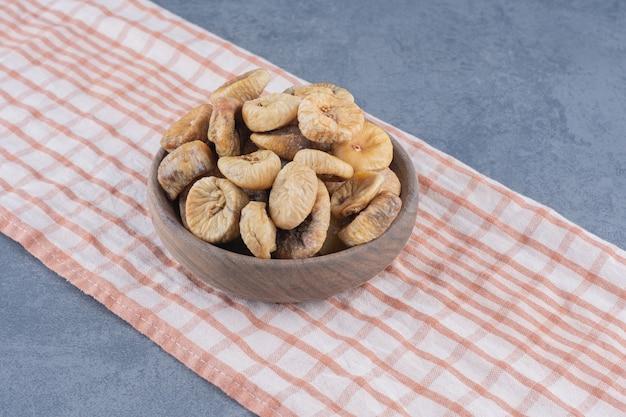Leckere getrocknete früchte in der schüssel auf dem handtuch, auf dem marmorhintergrund.