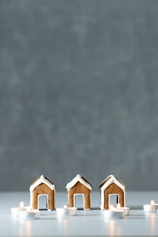 Leckere glasierte gemalte lebkuchenhäuser und kerzen auf grauem hintergrund. vertikaler rahmen. speicherplatz kopieren