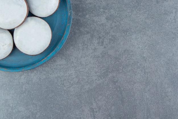 Leckere glasierte kekse auf blauem teller.