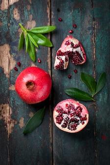 Leckere granatapfel mit grünen blättern