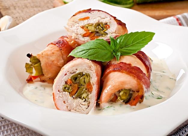 Leckere hähnchenbrötchen gefüllt mit grünen bohnen und karotten, eingewickelt in speckstreifen