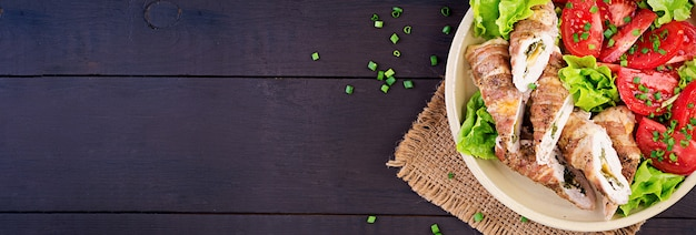 Leckere hähnchenbrötchen gefüllt mit käse und spinat, eingewickelt in speckstreifen. draufsicht