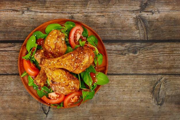 Leckere hähnchenkeulen mit spinat und tomate auf hölzernem hintergrund.